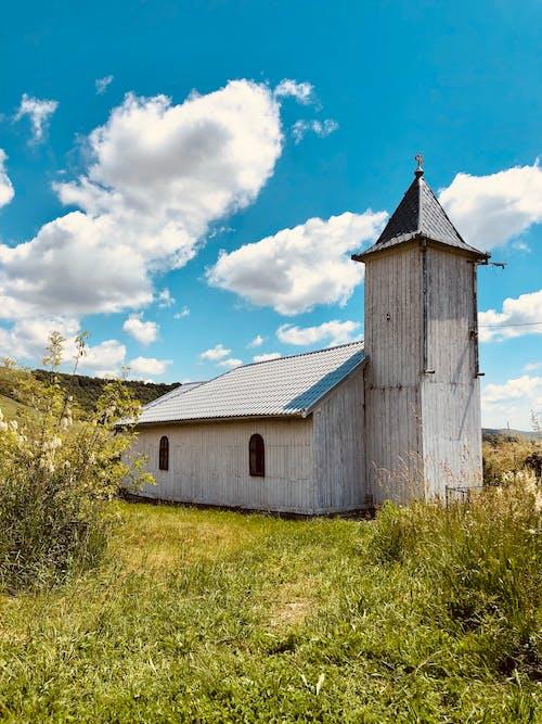Wooden Church on Green Grass Field Under Blue Sky