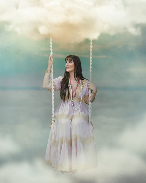Foto profissional grátis de balanço, mulher, nuvens