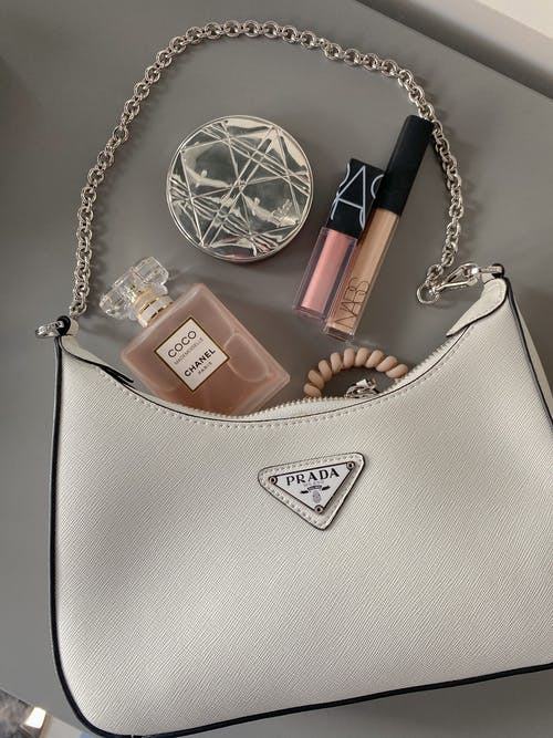 Flatlay Shot of a Bag with Makeup and Perfume