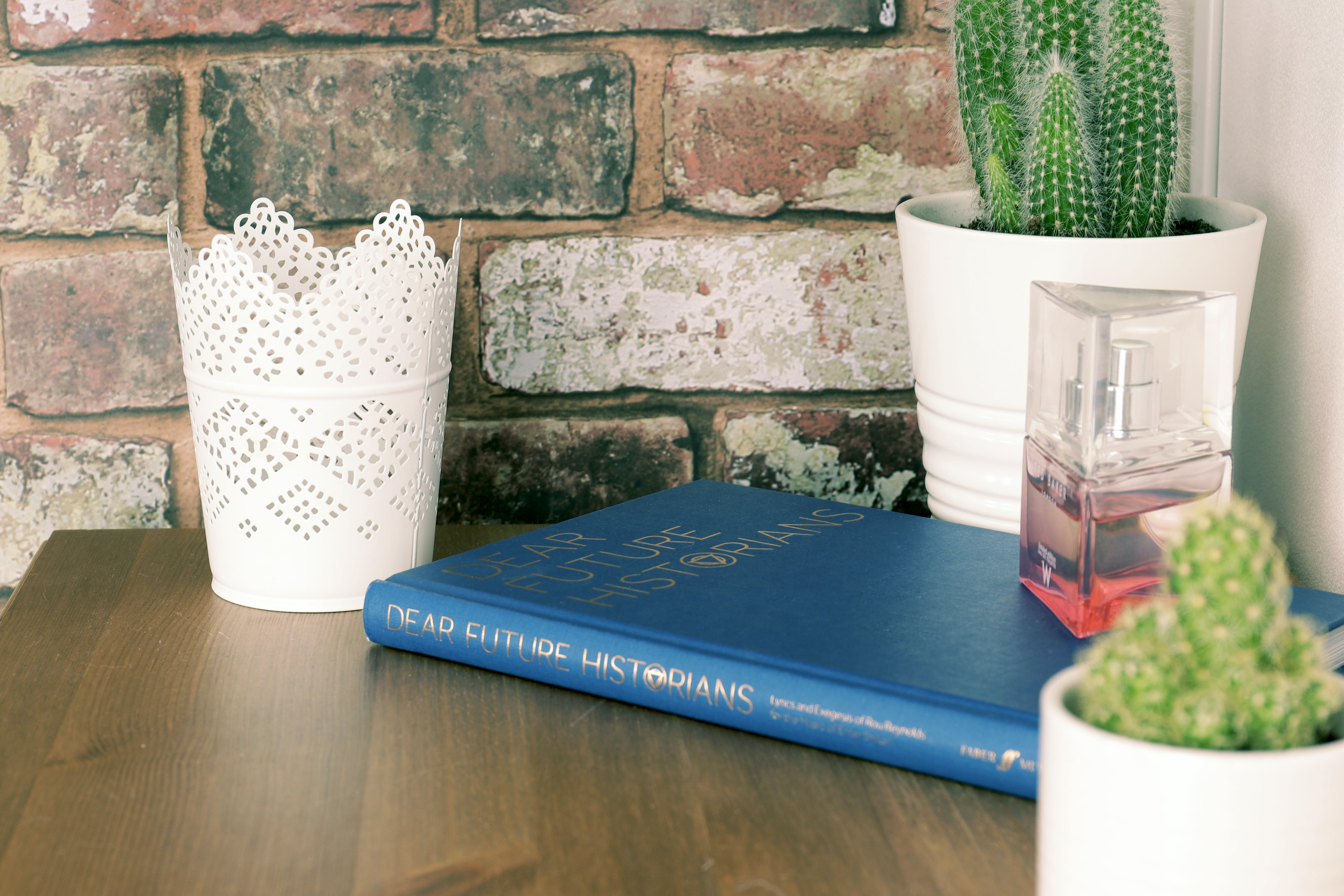 Blue Book on Brown Wooden Table with flower vases