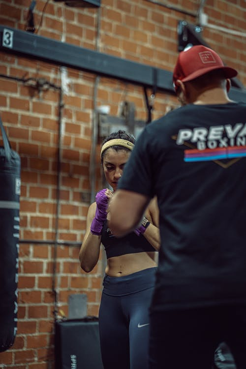 Concentrate ethnic female boxer in activewear training with unrecognizable instructor in cap in gym in daytime