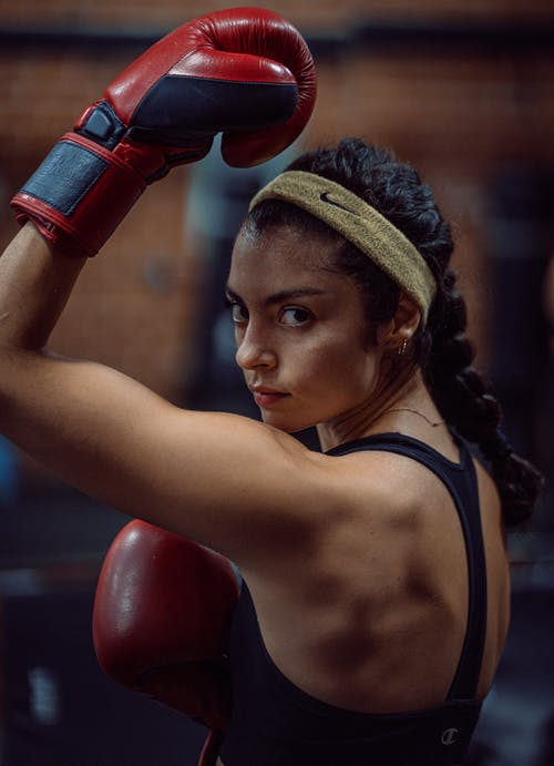 Ethnic sportswoman in boxing gloves looking at camera