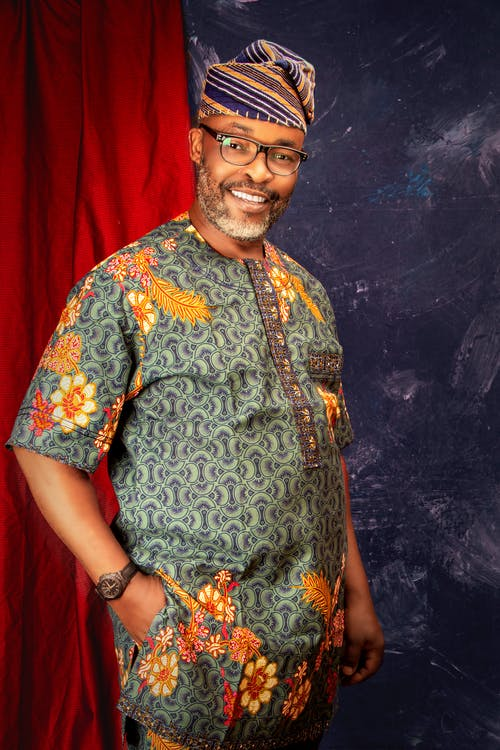 Positive African American man in ethnic outfit smiling at camera in studio