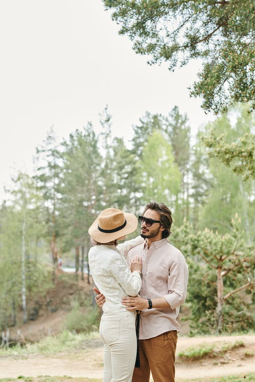 Man in White Dress Shirt and Brown Hat Kissing Woman in White Long Sleeve Shirt