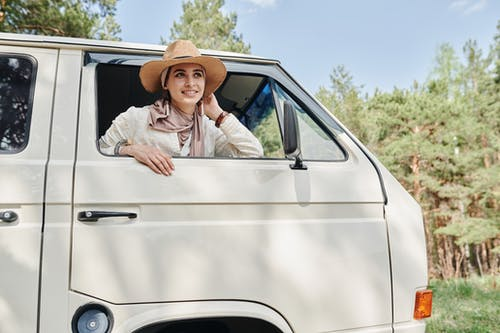 Man in White Dress Shirt and Brown Hat Sitting on White Car