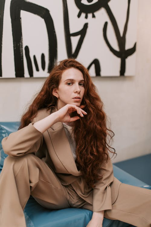 Woman in Brown Coat Sitting on Blue Couch