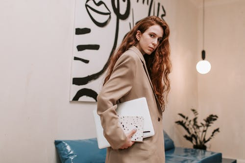 Woman in Brown Coat Holding Laptop Computer