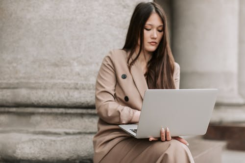 Woman in Brown Coat Sitting on Concrete Bench Using Macbook