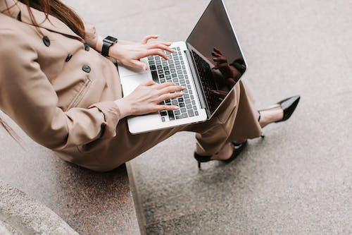 Person in Brown Coat Using Macbook Pro