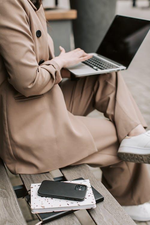 Woman in Brown Robe Using Macbook Air