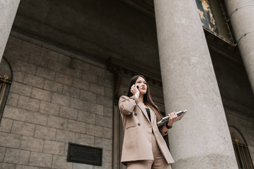 Woman in Brown Coat Holding Black and White Book