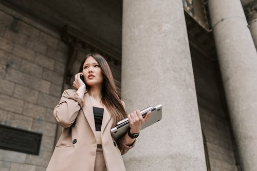 Woman in Brown Coat Holding Gray Smartphone