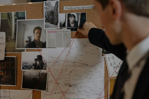 Man in Black Long Sleeve Suit Looking at Photographs on the Wall