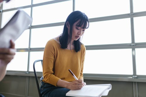 Woman in Orange Long Sleeve Shirt Sitting on Chair while Writing