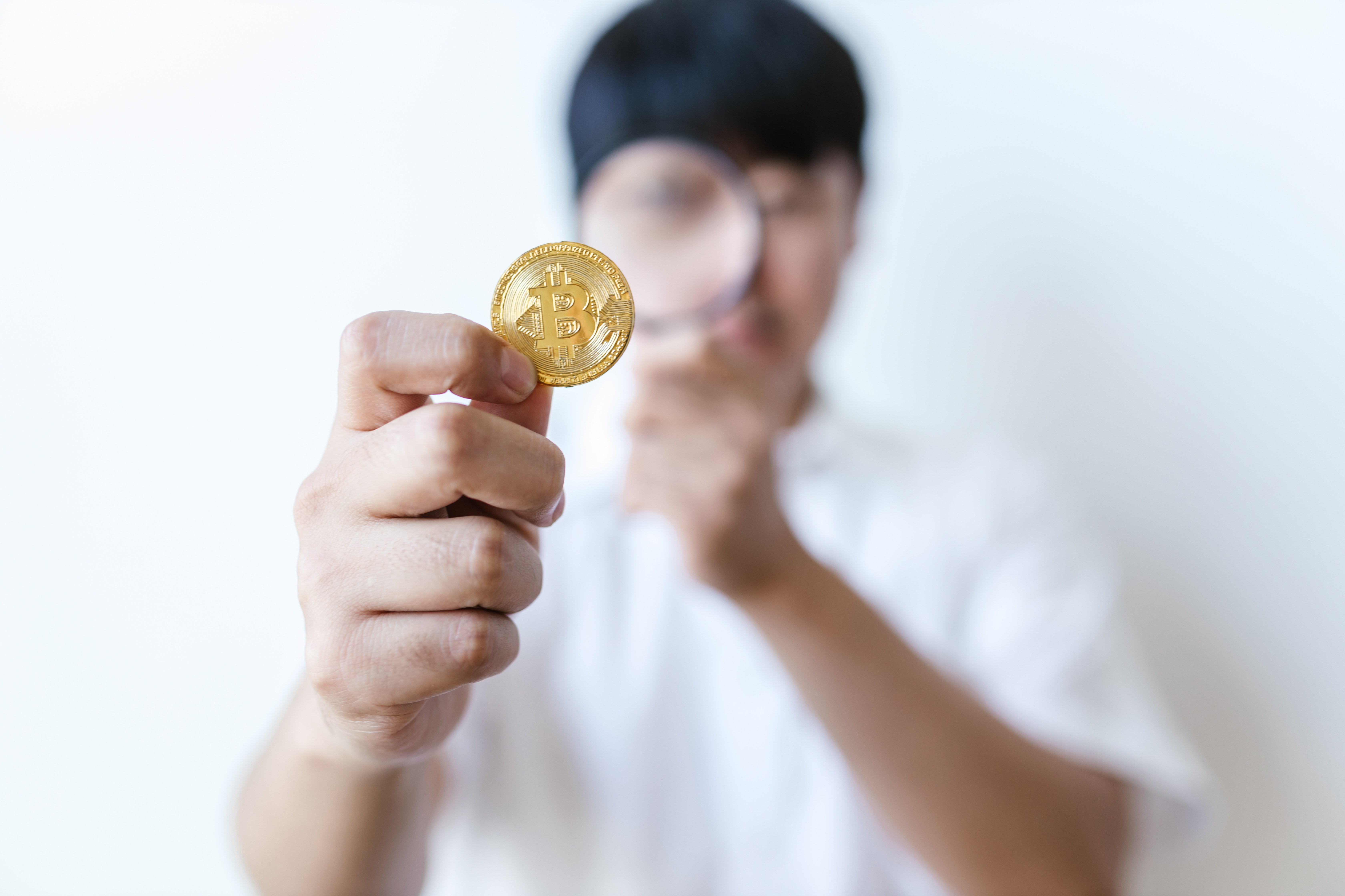 man in white shirt holding gold round coin