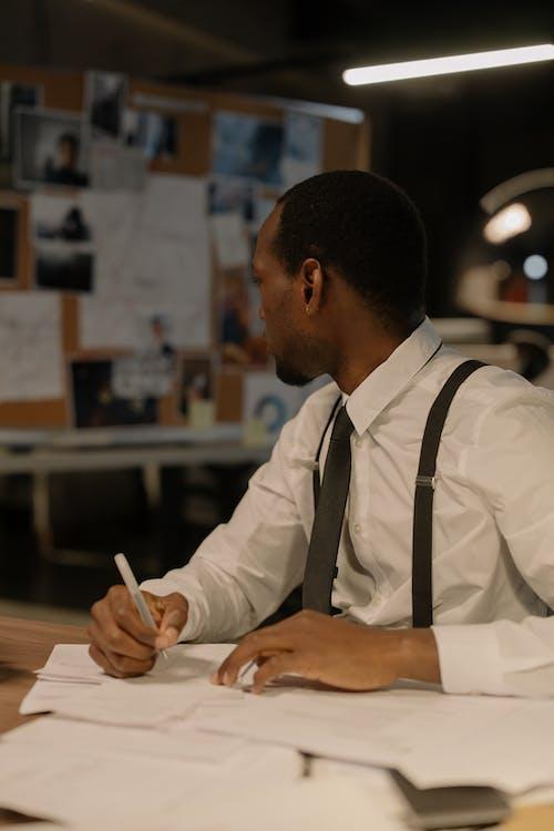 Man in White Dress Shirt Writing on White Paper