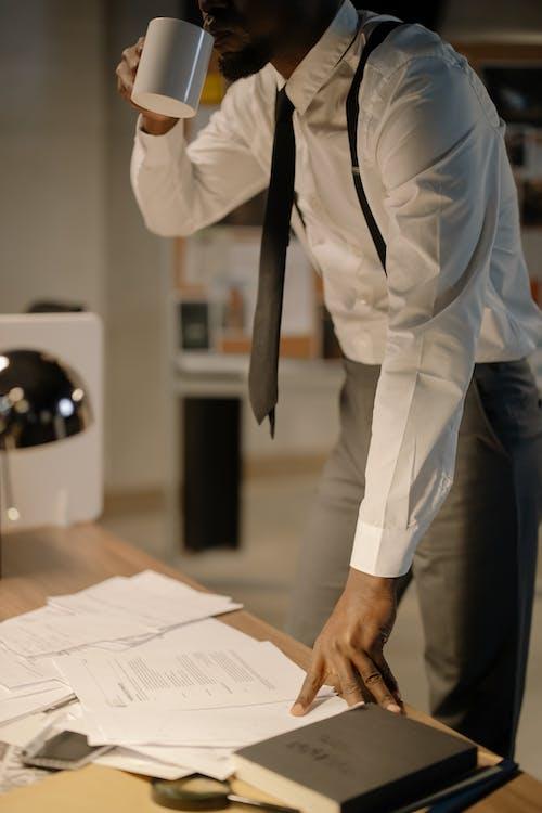 Man in White Shirt and Black Necktie Drinking from White Mug