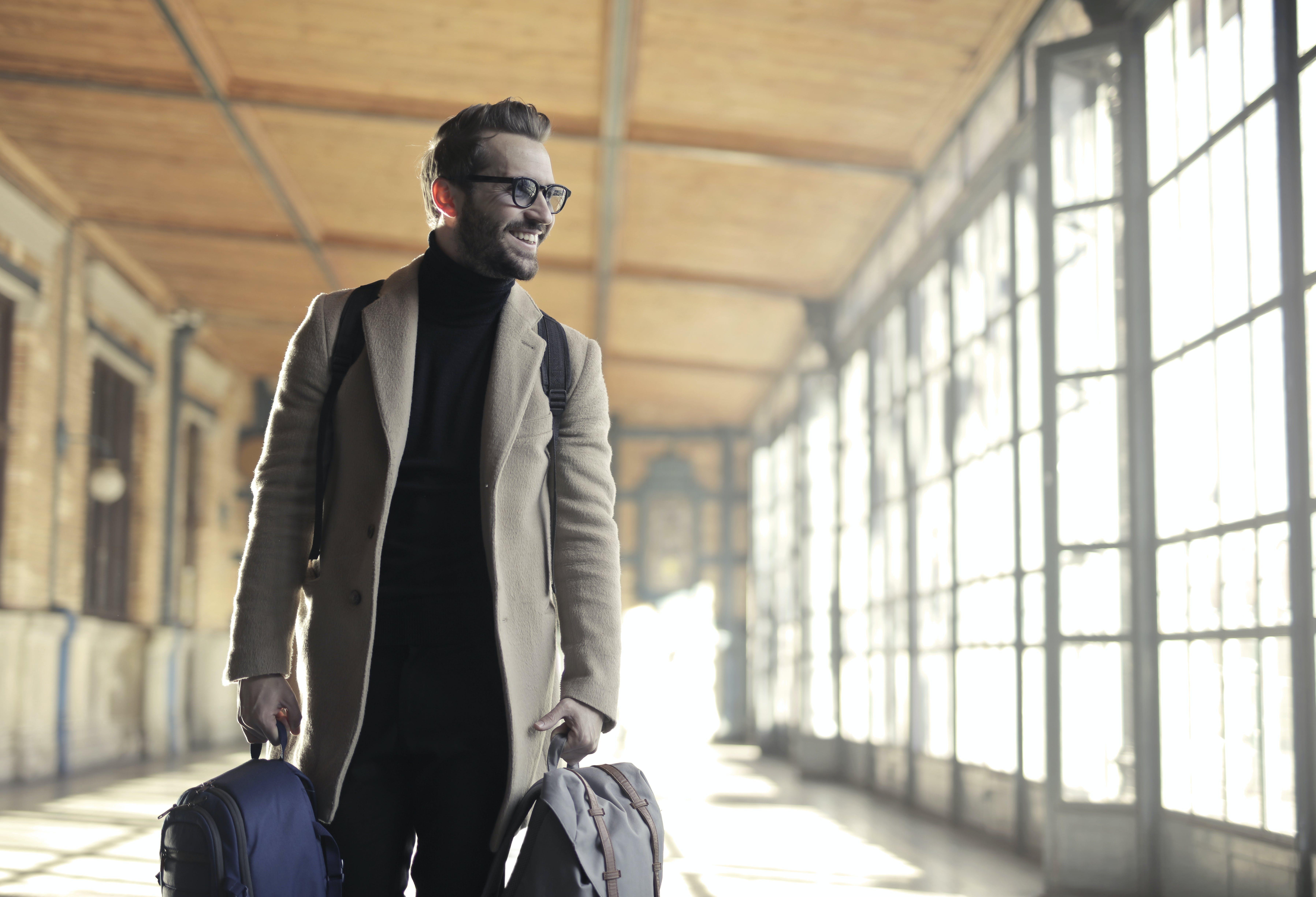 Man in Brown Robe Carrying Bag Smiling