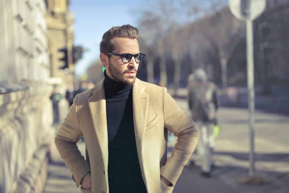 Selective focus photo of man wearing black turtleneck top with jacket on road
