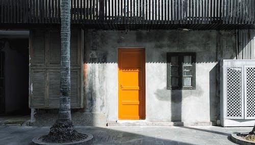 Orange Door on Gray Concrete Building