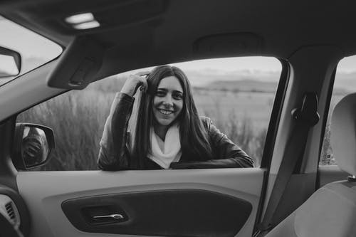 Grayscale Photo of Woman in Car