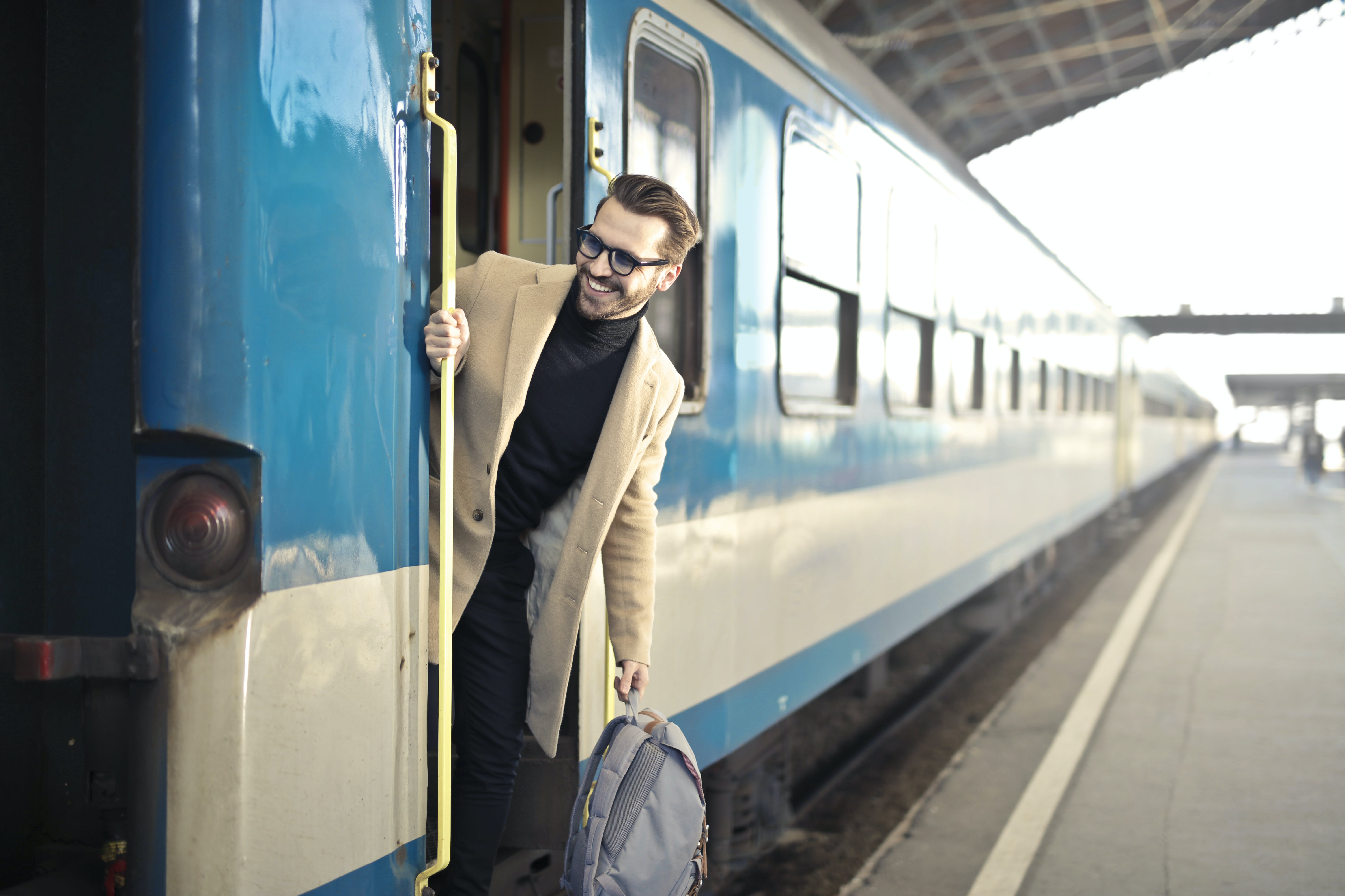 Man Wearing Beige Overcoat Inside Train