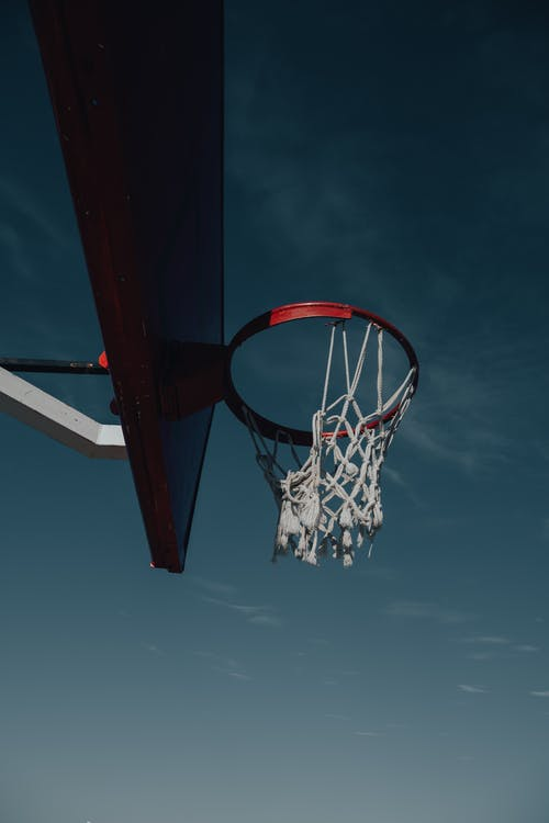 Red and White Basketball Hoop Under Blue Sky