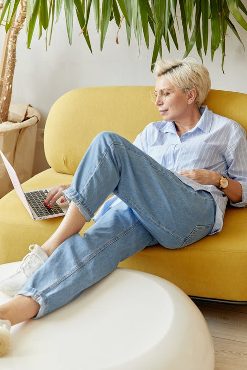Pretty Woman Sitting on a Yellow Sofa While Using Laptop