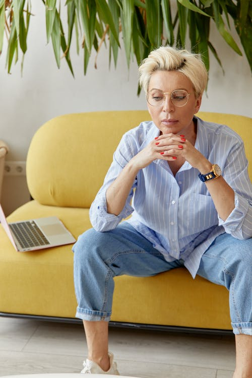 Woman Sitting on a Sofa Beside a Laptop