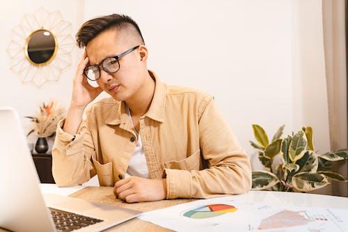 Man in Brown Shirt Wearing Eyeglasses Using a Laptop