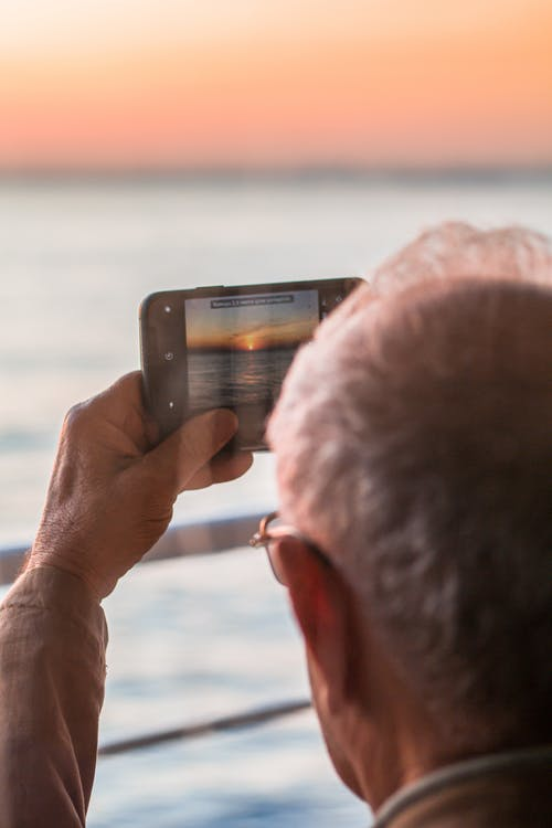 Anonymous male taking photo of ocean on smartphone at sunset