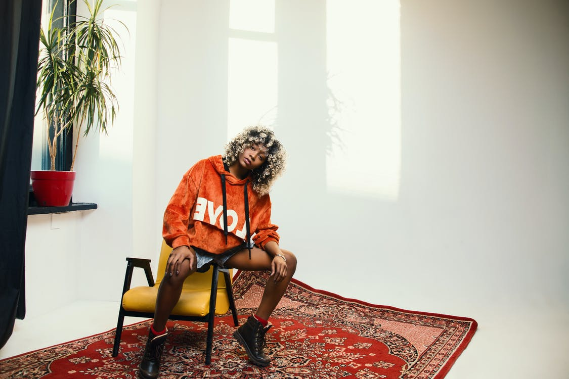 Woman Wearing Orange Pullover Hoodie Sitting on Chair's Arm