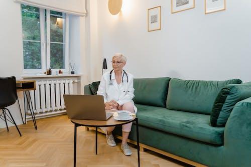 Woman in White Blazer Sitting on Green Sofa
