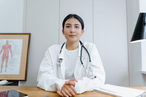 Woman in White Scrub Suit Wearing Black Stethoscope