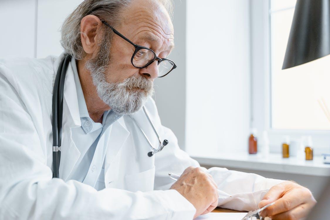 Man in White Scrub Suit Wearing Black Framed Eyeglasses