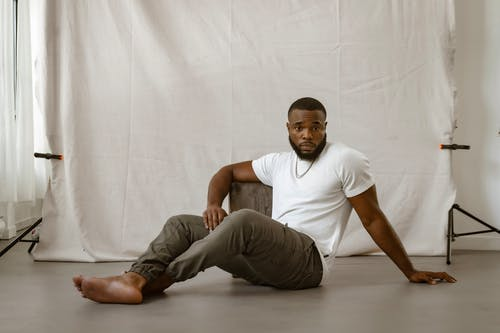 Man in White Shirt and Brown Pants Sitting on the Floor