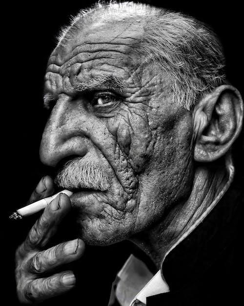 Grayscale Photo of a Man Smoking a Cigarette