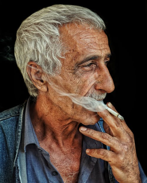 An Elderly Man Smoking a Cigarette
