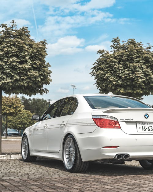 White BMW Car Parked Near a Tree