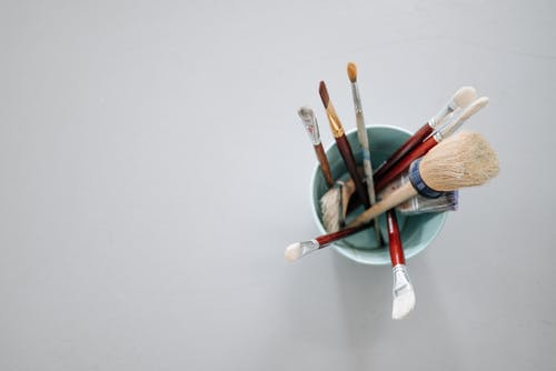 Paint Brushes in the Bucket over a White Surface