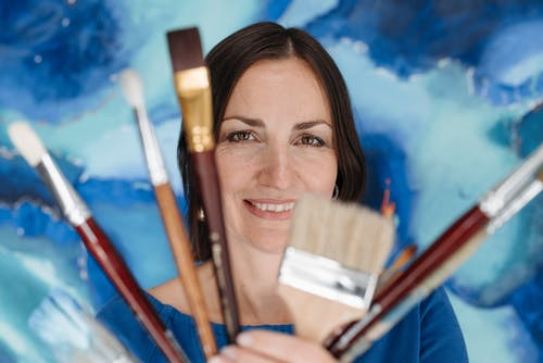 Woman Holding Brushes on Her Face