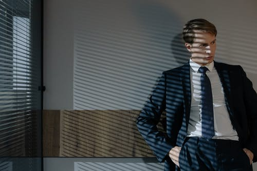 A Man in Business Suit Standing by the Glass Window