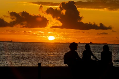 Silhouette of 2 People Sitting on Bench during Sunset