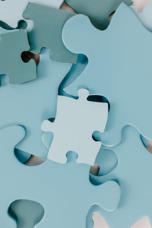 Gray Puzzle Piece on White Surface