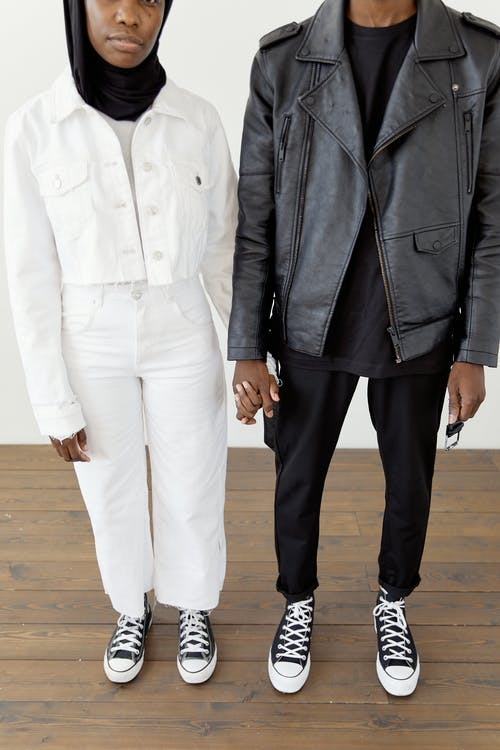 A Couple Standing on the Wooden Floor while Holding Hands
