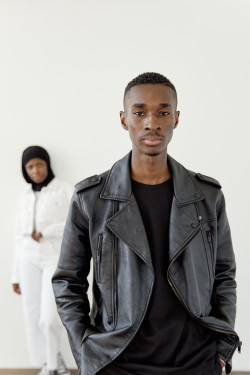 A Man Wearing Leather Jacket and a Woman in Black Hijab