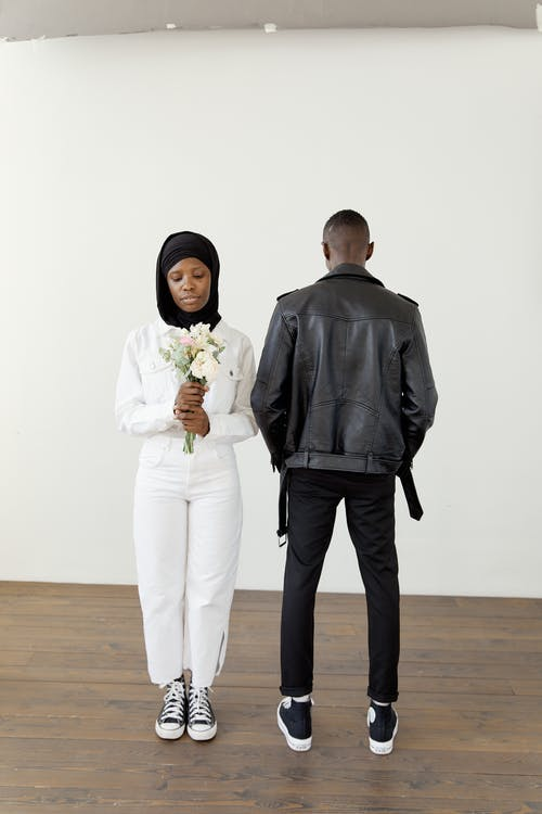 A Woman in Black Hijab Holding a White Bouquet and a Man in Black Jacket Facing Backwards