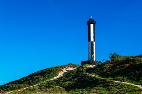 White and Black Lighthouse on Green Grass Field Under Blue Sky