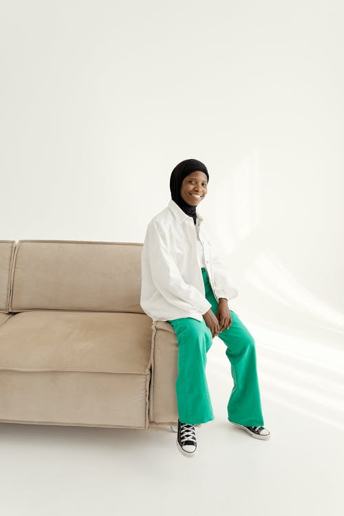 Woman in White Long Sleeves and Green Pants Sitting on Beige Sofa