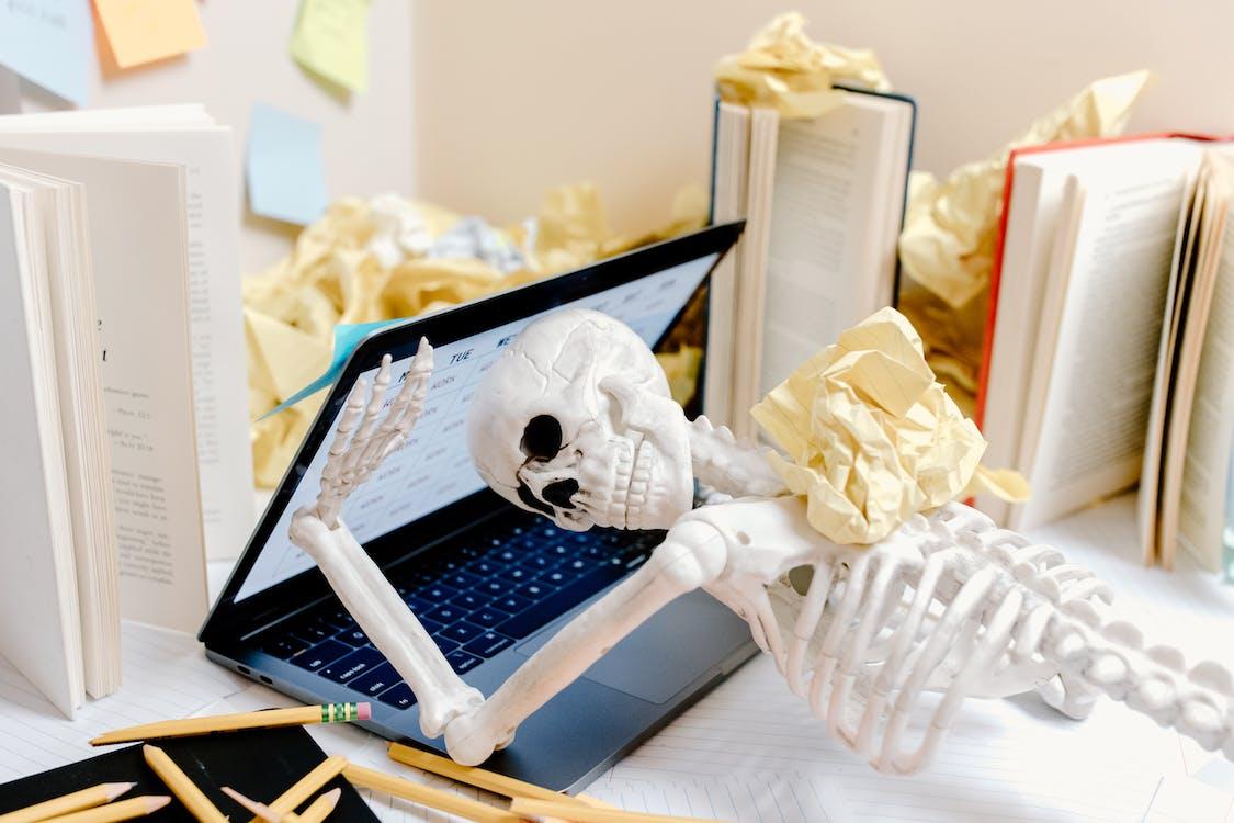 White Skull Figurine on Black Laptop Computer